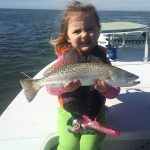 very young girl catches a speckled trout